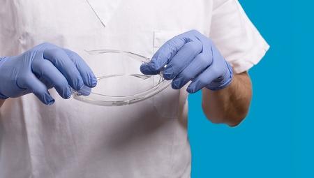 Γιατρός που κρατάει προστατευτικά γυαλιά